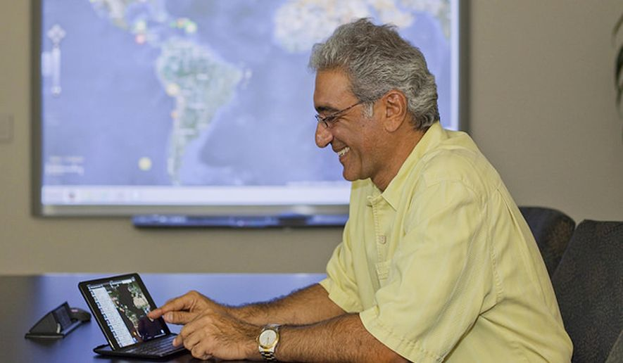 In this February 2013 photo provided by the Pacific Disaster Center, Ray Shirkhodai, executive director of the Pacific Disaster Center, demonstrates how to use the mobile app, Disaster Alert, at the center based in Kihei, Hawaii. A Zika outbreak has taken hold in Latin America, but researchers thousands of miles away in Hawaii are trying to figure out where it might spread. Researchers from the University of Hawaii at the Pacific Disaster Center are working with data to show where the virus might spread, and which countries might need more help to combat it. (Pacific Disaster Center via AP)
