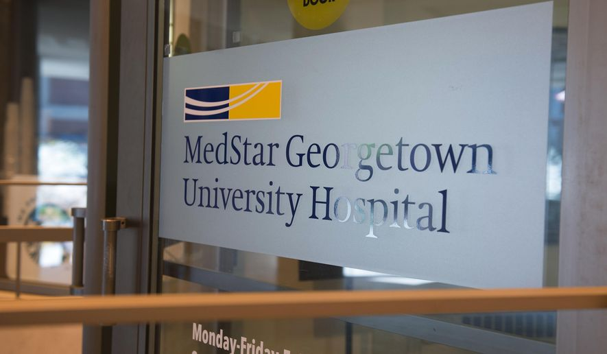 FILE - In this March 28, 2016 file photo, a sign covers the door to MedStar Georgetown University Hospital in Washington. The hackers who seriously disrupted operations at a large hospital chain for days and held its data hostage broke into a computer server left vulnerable on its corporate network despite urgent public warnings since at least 2007 that it needed to be fixed with a simple update, The Associated Press has learned.  (AP Photo/Molly Riley, File)