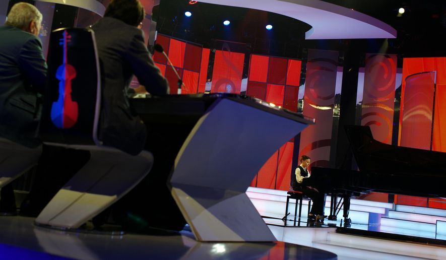 Young classical musician and competitor of the 'Virtuosos' talent show, Lajos Tamas Petres plays for the jury on a piano during the recording of the show in the studio of the Hungarian State Television in Budapest, Hungary on Saturday April 2, 2016. The creators of 'Virtuosos' have signed a deal with Dick Clark Productions, producers of the American Music Awards and many other shows, to license the format of the successful program internationally. (AP Photo/Bela Szandelszky)