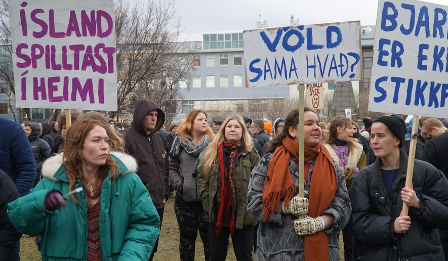 People hold banners and protest in front of Parliament building in Reykjavik, Iceland, Tuesday April 5, 2016. The leak of millions of records on offshore accounts claims its first high-profile victim as Iceland's prime minister Sigmundur David Gunnlaugsson resigns amid outrage over revelations he used such a shell company to conceal a conflict of interest. (AP Photo/David Keyton)
