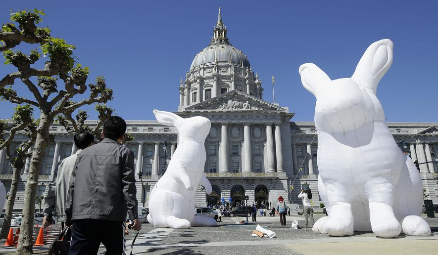 "Pedestrians look toward large illuminated rabbits installed at Civic Center Plaza as part of an art piece entitled ""Intrude"" by Australian artist Amanda Parer, across from City Hall in San Francisco, Tuesday, April 5, 2016. To prevent the kind of vandalism that hit Super Bowl 50 artwork earlier this year, the bunnies will get 24-hour security from now until the exhibit ends on April 25. (AP Photo/Jeff Chiu)"