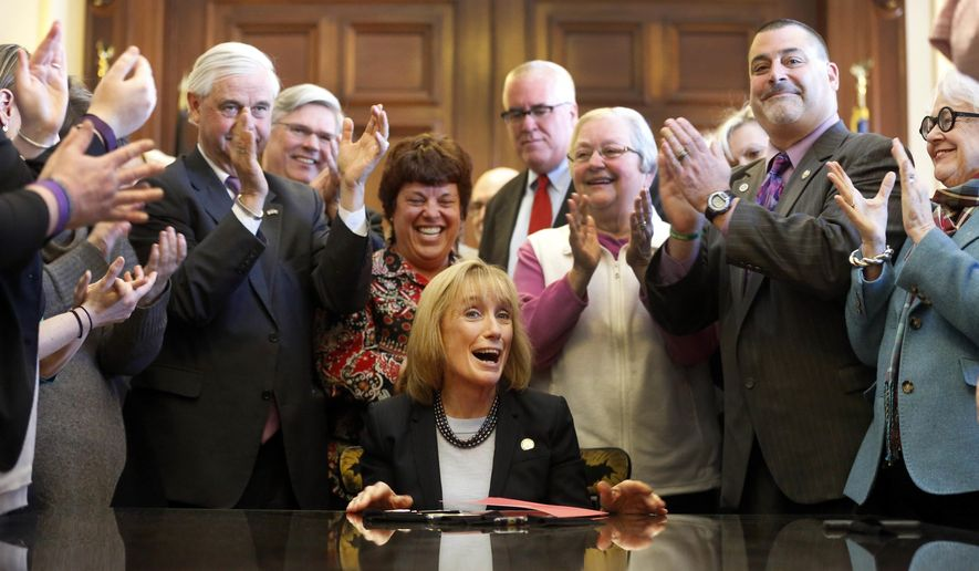 New Hampshire Gov. Maggie Hassan, seated, is applauded by supporters after signing into law a Medicaid expansion bill, Tuesday April 5, 2016, at the Statehouse in Concord, N.H. The bill allows nearly 50,000 New Hampshire residents to keep their health care for another two years. (AP Photo/Jim Cole)