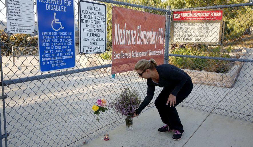 Terri Gaspar places flowers at Madrona Elementary School, where a homemade model rocket exploded, killing at least one high school student, in Thousand Oaks, Calif., Tuesday, April 5, 2016. Investigators will try to piece together a homemade model rocket to figure out why it exploded at a Southern California school, killing a high school student and sending his friend to a hospital with minor injuries, authorities said Tuesday. (Al Seib/Los Angeles Times via AP) MANDATORY CREDIT