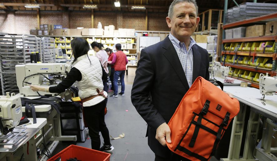 Founder and CEO Mark Dwight holds a backpack while posing at his Rickshaw Bagworks factory on Monday, April 4, 2016, in San Francisco. The San Francisco Board of Supervisors is voting on whether to require six weeks of fully paid leave for new parents - a move that would be a first for any jurisdiction. The proposal to be voted on Tuesday would require San Francisco employers with at least 20 employees to make up the rest. (AP Photo/Eric Risberg)