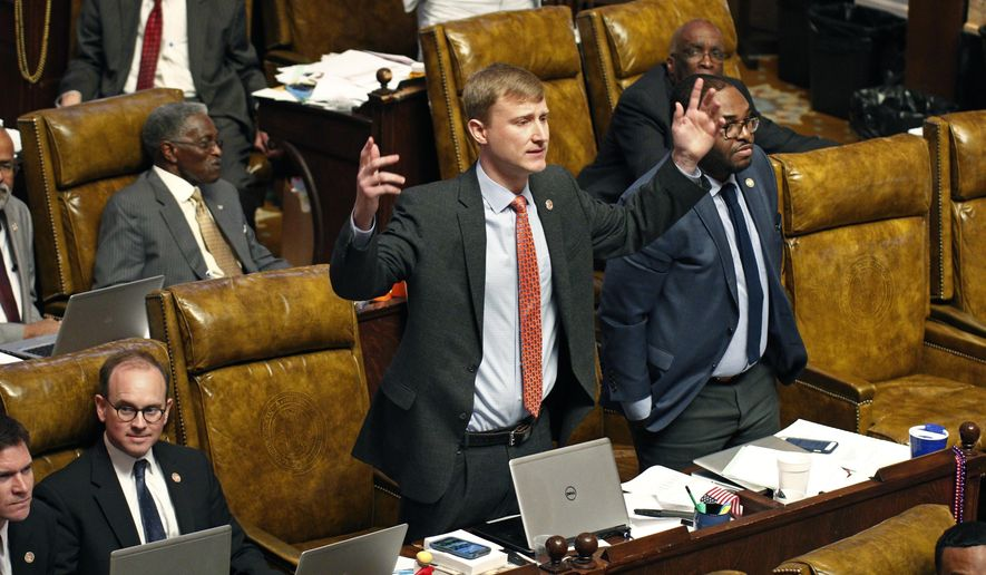 Rep. Joel Bomgar, R-Madison, center, tries to rally support for a electronic roll call vote instead of a voice vote during debate on amendments in the House over a Senate bill tax cut Tuesday, April 5, 2016, at the Capitol in Jackson, Miss. Rowmate Rep. Jarvis Dortch, D-Raymond, right, stands in support. (AP Photo/Rogelio V. Solis)