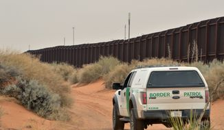 In this Jan. 4, 2016, file photo, a U.S. Border Patrol agent drives near the U.S.-Mexico border fence in Santa Teresa, N.M. (AP Photo/Russell Contreras, File)