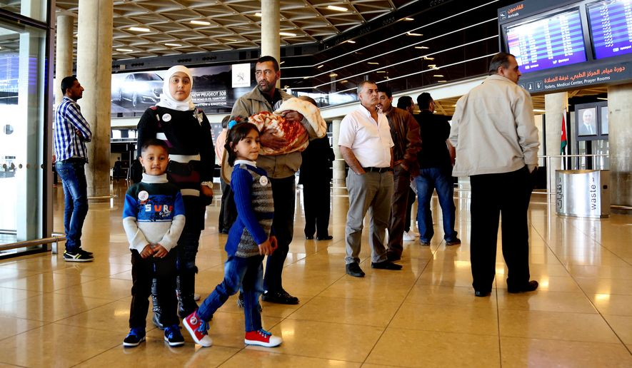 """Syrian refugee Ahmad al-Abboud, center, waits with his family at the International Airport of Amman, Jordan, Wednesday, April 6, 2016. The first Syrian family to be resettled to the U.S. under its speeded-up """"surge operation"""" departed to the United States Wednesday from the Jordanian capital, Amman. Al-Abboud, who is being resettled with his wife and five children, said that although he is thankful to Jordan — where he has lived for three years after fleeing Syria's civil war — he is hopeful of finding a better life in the U.S. (AP Photo/Raad Adayleh)"""