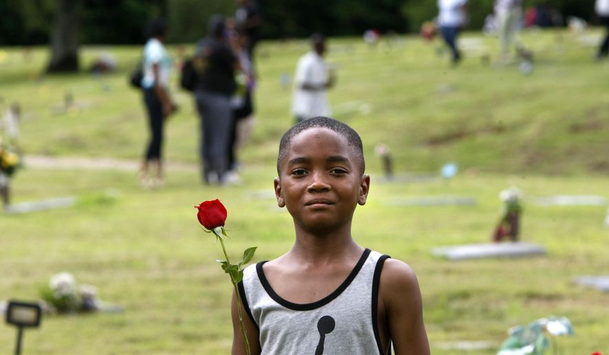 ADVANCE FOR USE MONDAY, APRIL 11, 2016 AND THEREAFTER - In this Monday, May 25, 2015 photo, Kendrick Cloyd, 8, holds a rose as he looks for the graves of his uncle and his sister at the Galilee Memorial Gardens cemetery in Memphis, Tenn. The cemetery was temporarily opened to visitors on Memorial Day. It was closed in 2014 after owner Jemar Lambert was accused of misplacing hundreds of bodies, burying multiple cadavers in the same grave, and crushing caskets to fit them into single plots. (AP Photo/Karen Pulfer Focht)