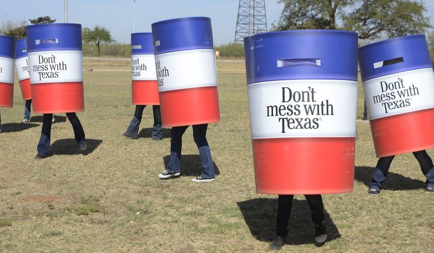 FILE - In this April 12, 2013 file photo, members of the Odessa College Cheer Team dress as trash cans and dance to the Don't Mess with Texas song during a news conference to promote Texas Department of Transportation's litter clean up 'can'paign in Midland, Texas. The Don't Mess With Texas anti-litter campaign has been around for 30 years with more chances to pick up trash across the state. (Mark Sterkel/The Odessa American, via AP, File)