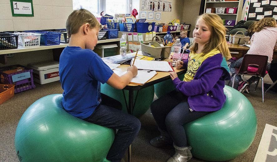 In this March 15, 2016 photo, second-graders Payton Rumfelt, 8, and Sarah Hutchison, 7, work together on a math assignment in Chelsea Stuart's class at Northside Elementary School in Morrison, Ill. Stuart has removed some of the tables, chairs and desks from her room and replaced them with wobble cushions, bean bags, pillows and exercise balls. (Michael Krabbenhoeft/The Daily Gazette via AP) MANDATORY CREDIT