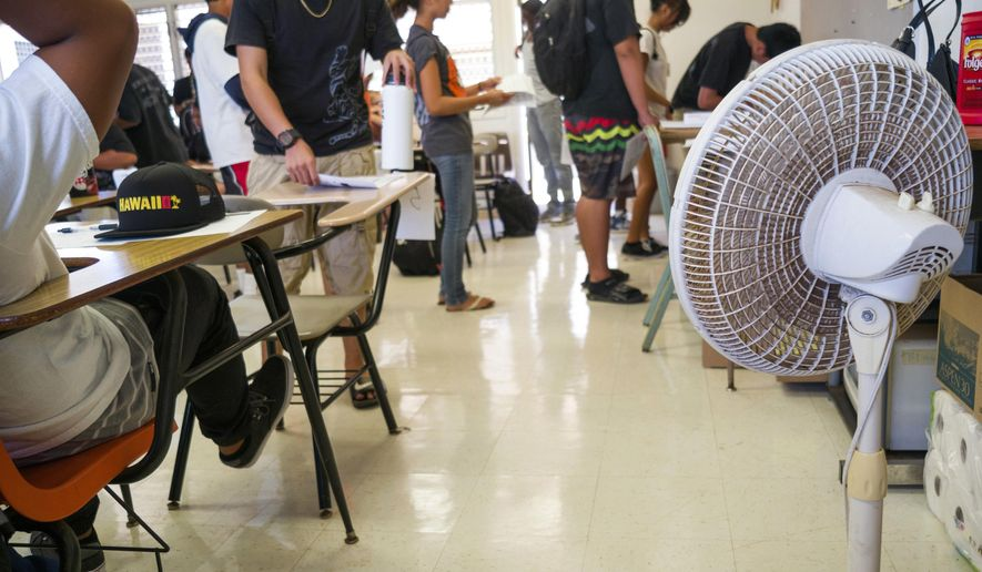 FILE - In this Aug. 3, 2015 file photo, with only open windows and fans to cool the room down, students enter their non air conditioned classroom at Campbell High School in Ewa, Hawaii. Most of Hawaii's public schools don't have air conditioning, and record-high temperatures have left teachers and students saying they can't focus because of the heat. Hawaii lawmakers are saying it's time to cool Hawaii's public schools. A proposal being considered by the House Committee of Finance would fund air conditioning for Hawaii Department of Education schools and expedite the process to get cooling systems installed in classrooms. (AP Photo/Marco Garcia, File)