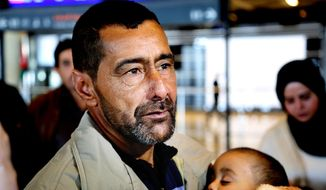 Syrian refugee Ahmad al-Abboud waits with his family at the International Airport of Amman, Jordan, Wednesday, April 6, 2016. (AP Photo/Raad Adayleh)