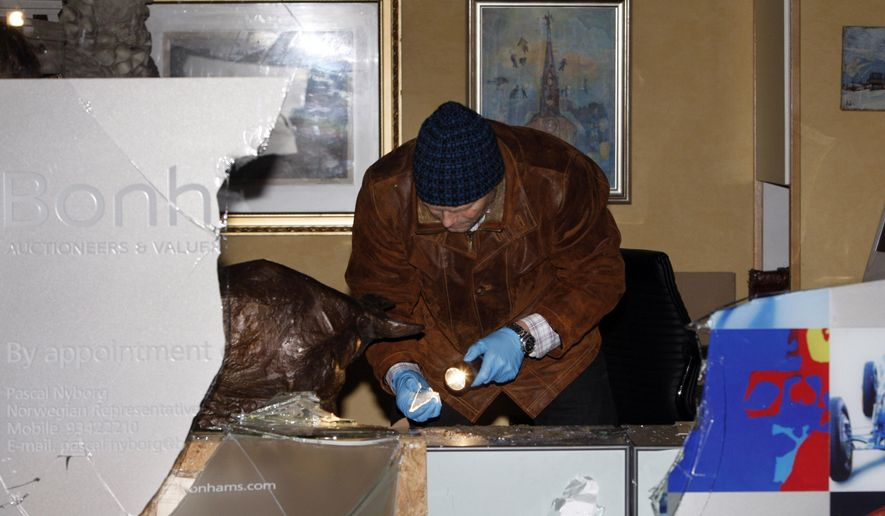 FILE - This is a Nov. 13, 2009 file photo of plain clothed  police officer on the scene of a burglary in central Oslo were a lithograph by Edvard Munch was stolen. Norwegian police say they have arrested 2 men in connection with the 2009 theft of a valuable artwork by Edvard Munch from an Oslo art dealer. Police spokeswoman Unni Groendal says the men are suspected of handling stolen goods and face a pre-trial detention later Wednesday April 6, 2016.  (Lise Aserud, NTB scanpix, File via AP) NORWAY OUT
