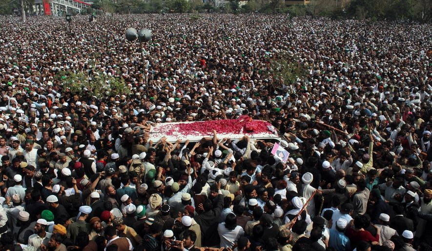 In this March 1, 2016, file photo, thousands of people attend a funeral of Pakistani police officer Mumtaz Qadri, the convicted killer of a former governor, in Rawalpindi, Pakistan. Tackling extremists is a political minefield in Pakistan, where politicians openly consort with leaders of banned militant groups, and sympathy exists within the security forces and civil administration for perpetrators of crimes committed in the name of religion. (AP Photo/Anjum Naveed, File)