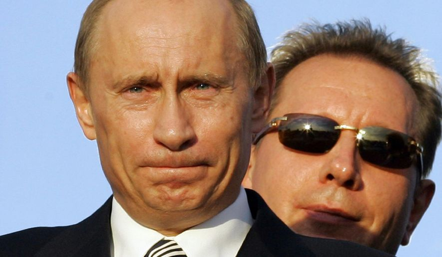 In this Saturday, June 9, 2007 file photo Russian President Vladimir Putin, with then head of his bodyguard service Viktor Zolotov in the back, watches the presentation of Sochi's bid for the 2014 Winter Olympics at the Economic Forum in St. Petersburg, Russia. (AP Photo/Dmitry Lovetsky, File)