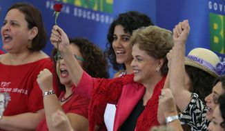 Brazil's President Dilma Rousseff raises a rose, during a Women in Defense of Democracy Meeting, at the Planalto Presidential Palace, in Brasilia, Brazil, Thursday, April 7, 2016. The women representing social movements and trade unions who are against Rousseff's removal from office, gathered to show their support. (AP Photo/Eraldo Peres) ** FILE **