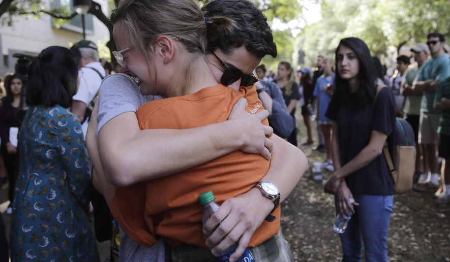 University of Texas students embrace during a gathering for fellow student Haruka Weiser on campus, Thursday, April 7, 2016, in Austin, Texas. Weiser, a first-year theater and dance student from Oregon, was found dead on campus after she was reporter missing earlier this week. (AP Photo/Eric Gay)