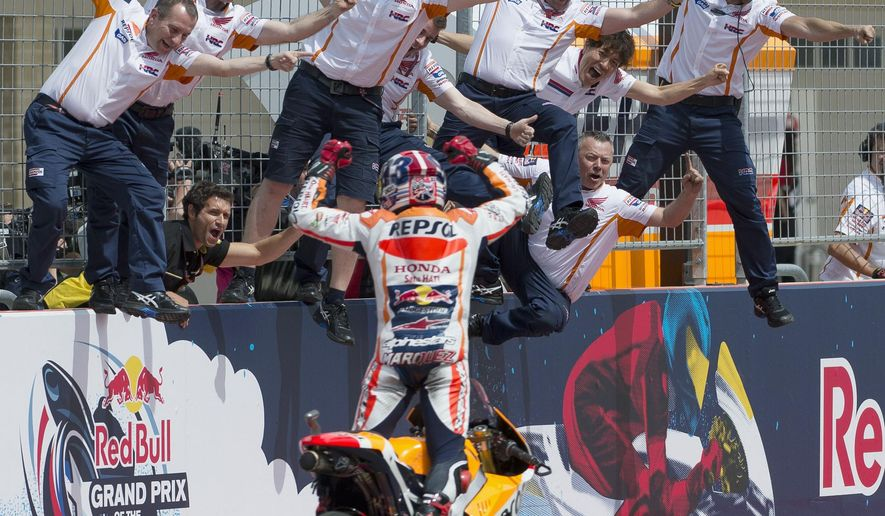 FILE - In this April 12, 2015, file photo, Marc Marquez, of Spain, rides by his crew after winning the MotoGP Grand Prix motorcycle race at the Circuit of the Americas in Austin, Texas. MotoGP has been filled with drama and crashes since the end of the 2015 season. Marc Marquez hopes to keep things quite boring at the Grand Prix of the Americas this week, where the Repsol Honda rider has won three years in a row. (AP Photo/Darren Abate, File)