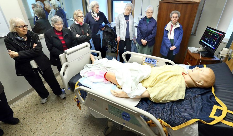 In this Monday, April 4, 2016, a group from the Franciscan Sisters of Perpetual Adoration tours a simulation room in the Sister Leclare Beres Learning and Resource Center during an open house, in La Crosse, Wis. (Erik Daily/La Crosse Tribune via AP) MANDATORY CREDIT