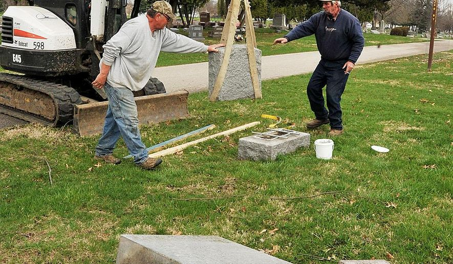 Greenwood Cemetery workers Jeremy Goddard, in the Bobcat, Norm Lamb, left, and Mike Pestle reset a headstone, on April 6, 2016 in Muscatine, Iowa.  Workers are fixing up to 30 headstones that were pushed off their pedestals at Greenwood Cemetery last weekend. Muscatine police are investigating the vandalism (Beth Van Zandt/Muscatine Journal via AP) MANDATORY CREDIT