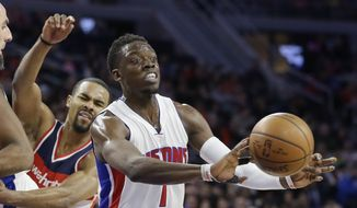 Detroit Pistons guard Reggie Jackson passes the ball as Washington Wizards guard Ramon Sessions closes in during the first half of an NBA basketball game Friday, April 8, 2016, in Auburn Hills, Mich. (AP Photo/Carlos Osorio)