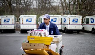 In this Feb. 7, 2013, file photo, a U.S. Postal Service letter carrier gathers mail to load into his truck before making his delivery run in the East Atlanta neighborhood in Atlanta. (AP Photo/David Goldman, File)