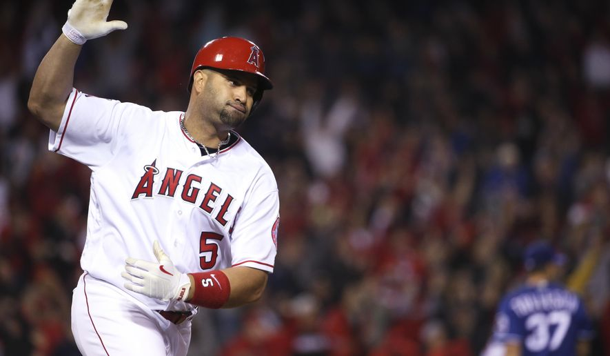 Los Angeles Angels' Albert Pujols starts to celebrate after a single to left with the bases loaded in the ninth inning to give the Angels a 4-3 victory over the Texas Rangers in a baseball game Thursday, April 7, 2016, in Anaheim, Calif. (AP Photo/Lenny Ignelzi)