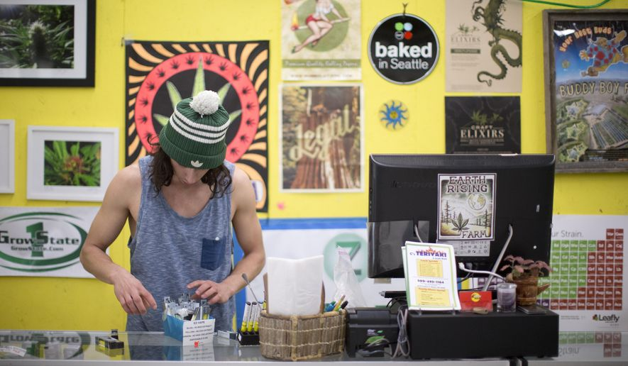 In this March 14, 2016 photo, Sky Stover, 22, works behind the counter at Margie's Pot Shop in Bingen, Wash. Recreational marijuana sales have declined at the store near the Washington state-Oregon border, since recreational marijuana began selling Oregon. (Beth Nakamura/The Oregonian via AP) MAGS OUT; TV OUT; NO LOCAL INTERNET; THE MERCURY OUT; WILLAMETTE WEEK OUT; PAMPLIN MEDIA GROUP OUT; MANDATORY CREDIT