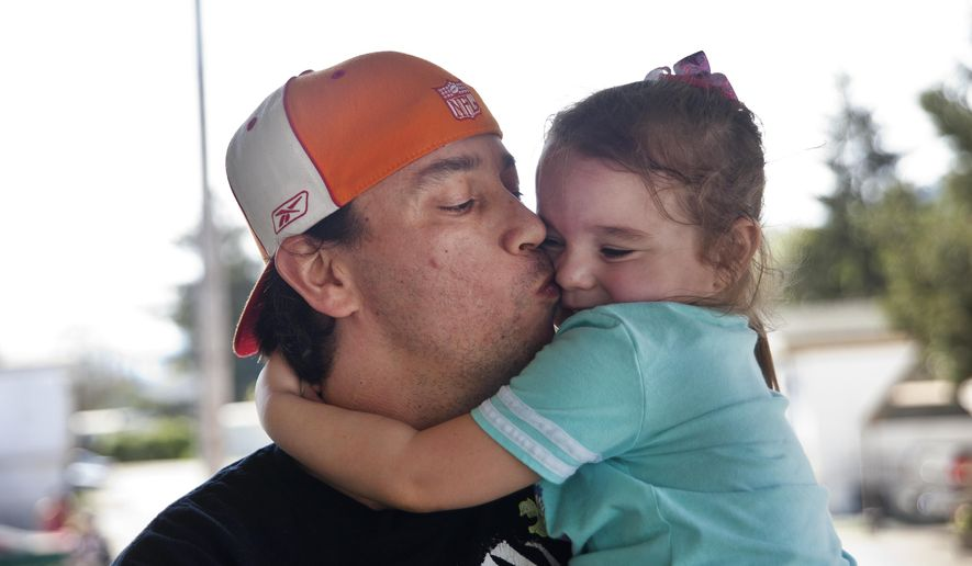 In this photo taken Saturday April 2, 2016,  Bryan Thouvenel gives his daughter Harmony Thouvenel, 5, a kiss while standing for a portrait in front of their home in Myrtle Creek, Ore. They had been apart nearly two years when Thouvenel, thanks to a tip from a friend, found his daughter and estranged ex-girlfriend at a Salvation Army homeless shelter in Spokane, Wash. (Katie Alaimo/The News-Review via AP) MANDATORY CREDIT