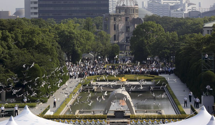 In this Aug. 6, 2015, file photo, doves fly over the cenotaph dedicated to the victims of the atomic bombing at the Hiroshima Peace Memorial Park during the ceremony to mark the 70th anniversary of the bombing in Hiroshima, western Japan. (AP Photo/Eugene Hoshiko, File)
