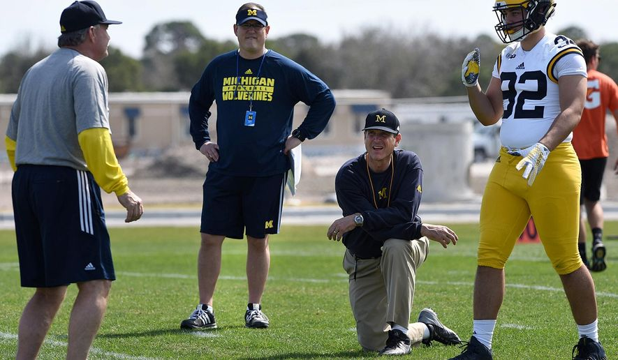FILE - In this Feb. 29, 2016, file photo, Michigan's head coach Jim Harbaugh, center right, watches defensive coordinator Don Brown, left, work with Cheyenn Robertson during team practice in Bradenton, Fla. The NCAA announced Friday, April 8, 2016,  that it was barring football coaches from holding camps or clinics on other campuses, siding with the Southeastern Conference in its high-profile dispute with Michigan's Jim Harbaugh. (Tiffany Tompkins/The Bradenton Herald via AP, File) MANDATORY CREDIT