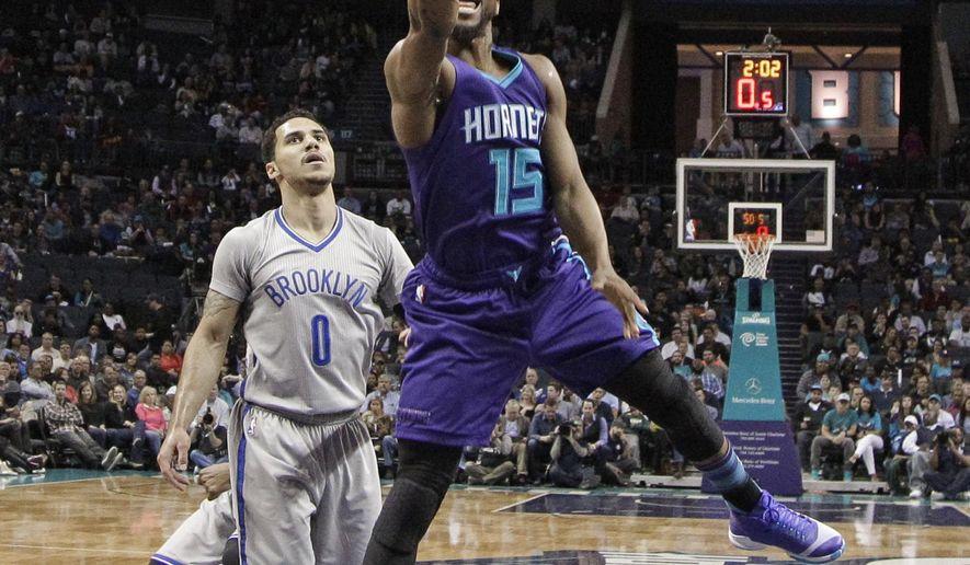 Charlotte Hornets' Kemba Walker (15) drives past Brooklyn Nets' Shane Larkin during the first half of an NBA basketball game in Charlotte, N.C., Friday, April 8, 2016. (AP Photo/Chuck Burton)