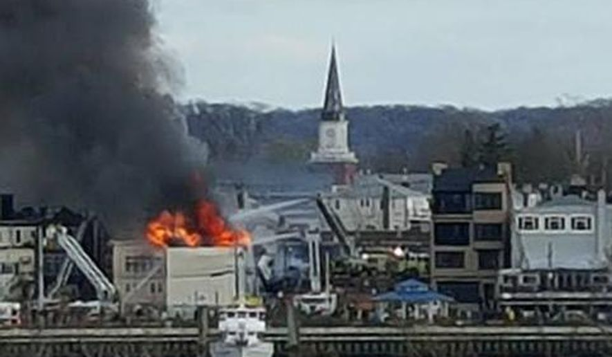 In this photo provided by Jeff Smith, fire rages from the roof of a building on the waterfront in Keyport, N.J., Friday, April 8, 2016. It wasn't immediately clear if anyone was injured in the blaze. (Jeff Smith via AP )