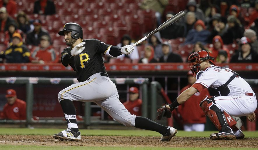 Pittsburgh Pirates' Francisco Cervelli hits a RBI single as Cincinnati Reds catcher Devin Mesoraco, right, looks on in the fifth inning of a baseball game, Friday, April 8, 2016, in Cincinnati. (AP Photo/John Minchillo)