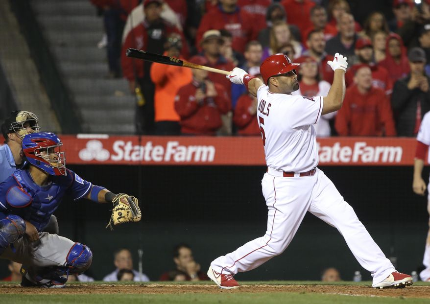 Los Angeles Angels' Albert Pujols watches his single to left with the bases loaded in the ninth inning to give the Angels a 4-3 victory over the Texas Rangers in a baseball game Thursday, April 7, 2016, in Anaheim, Calif.  (AP Photo/Lenny Ignelzi)