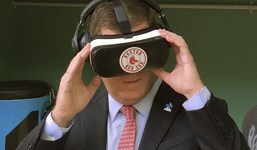 Boston Mayor Marty Walsh tries out a virtual reality device during a tour of the latest improvements at Fenway Park Friday, April 8, 2016, in Boston, in advance of Monday's Boston Red Sox home opener against the Baltimore Orioles. The free, two-minute virtual reality video shows scenes of batting practice and pitchers mound sessions from up close, with the viewer standing in the batters box or behind infielders as they take ground balls. Initially three dugout-themed booths will be stationed in the ballpark, each with several headsets. The club plans to also take the technology to schools and to other off-site events. (AP Photo/Jimmy Golen)