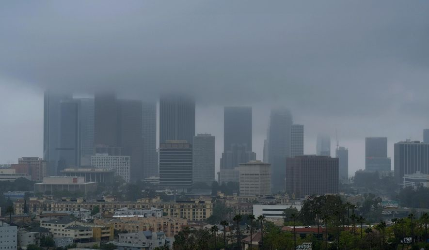 Heavy clouds and rain pass over downtown Los Angeles on Friday, April 8, 2016. The first of two weather systems has brought showers to Southern California but rainfall has been scattered and mostly light. The National Weather Service says radar shows showers running across the region early Friday but not much of the rain is reaching the ground. (AP Photo/Richard Vogel)