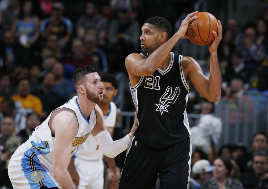San Antonio Spurs center Tim Duncan, right, looks to pass the ball as Denver Nuggets center Jusuf Nurkic, of Bosnia, defends in the first half of an NBA basketball game Friday, April 8, 2016, in Denver. (AP Photo/David Zalubowski)