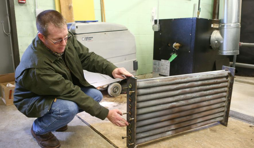 In this Tuesday, Feb. 23, 2016 photo, Jon Bearden, director of buildings and grounds at Eastern Howard School Corp., in Greentown, Ind., points out corroded pipes on the heat exchanger in the boiler room of the school. After having its water tested the school  found elevated lead levels in the water coming from some of its sinks and drinking fountains and temporarily stopped its 1,500 students from using that water in February. (Kelly Lafferty Gerber/The Kokomo Tribune via AP) MANDATORY CREDIT