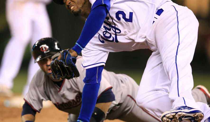 Kansas City Royals shortstop Alcides Escobar (2) falls over Minnesota Twins' Brian Dozier during a rundown between second and third bases in the ninth inning of a baseball game at Kauffman Stadium in Kansas City, Mo., Friday, April 8, 2016. Dozier was out on the play. The Royals defeated the Twins 4-3. (AP Photo/Orlin Wagner)