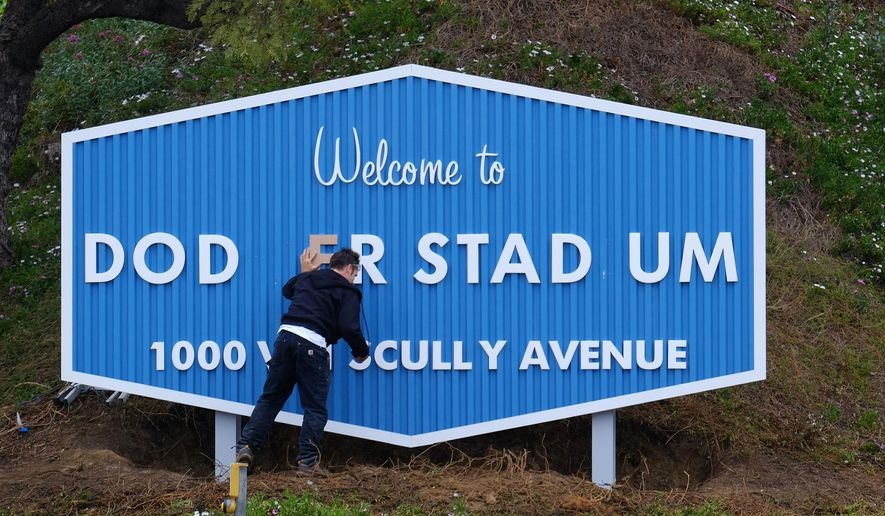 A worker affixes lettering onto a new sign at the entrance to Dodger Stadium on Friday, April 8, 2016, in Los Angeles. The Los Angeles City Council has moved to officially rename Elysian Park Avenue as Vin Scully Avenue, in honor of the Dodgers' longtime sportscaster. (AP Photo/Richard Vogel)
