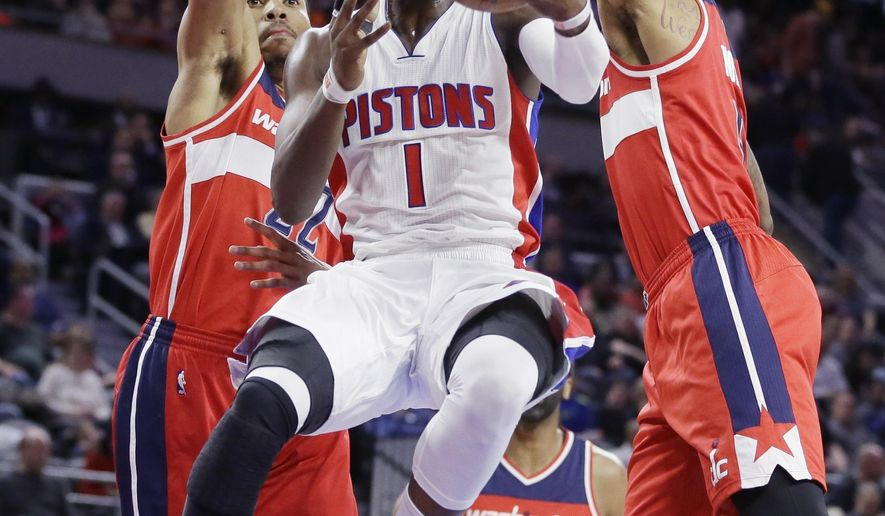 Detroit Pistons guard Reggie Jackson (1) makes a layup while defended by Washington Wizards forwards Otto Porter Jr., left, and Markieff Morris during the first half of an NBA basketball game Friday, April 8, 2016, in Auburn Hills, Mich. (AP Photo/Carlos Osorio)