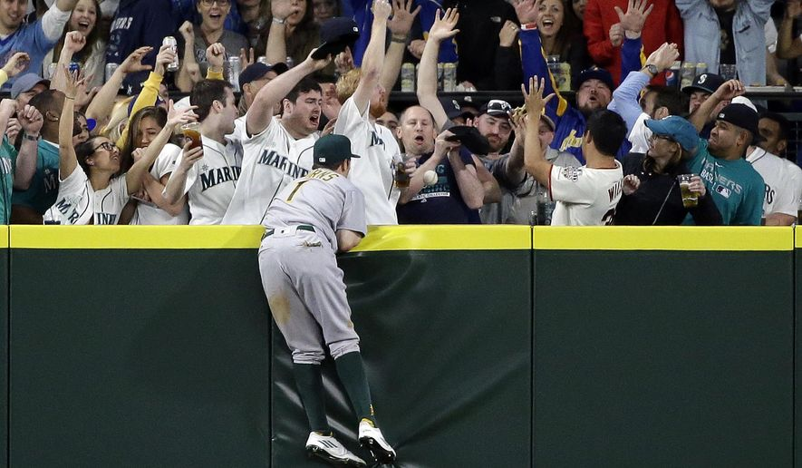 Oakland Athletics center fielder Billy Burns watches a fan drop the home run ball of Seattle Mariners' Dae-Ho Lee during the fifth inning of a baseball game Friday, April 8, 2016, in Seattle. (AP Photo/Elaine Thompson)