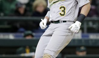 Oakland Athletics' Chris Coghlan touches home on his home run druing the ninth inning of a baseball game against the Seattle Mariners on Friday, April 8, 2016, in Seattle. (AP Photo/Elaine Thompson)