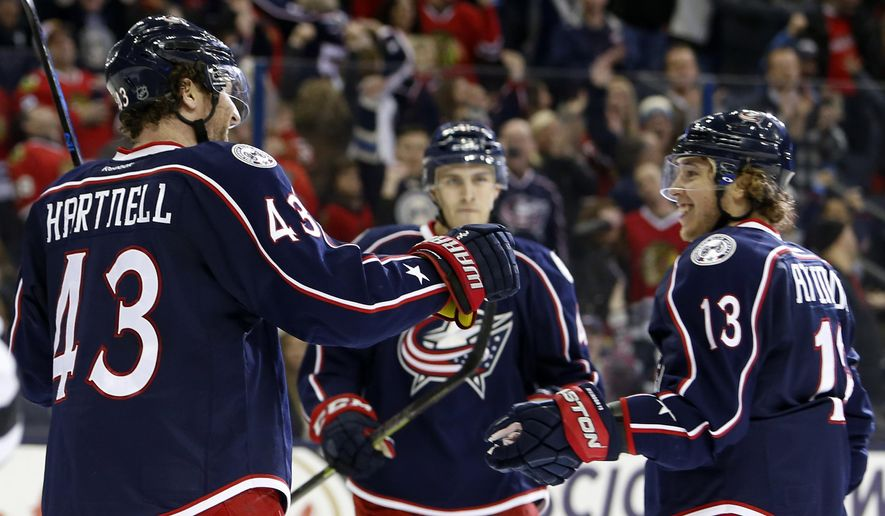 Columbus Blue Jackets' Scott Hartnell, left, celebrates his game-winning goal against the Chicago Blackhawks withteammates Cam Atkinson, left, and Alexander Wennberg, of Sweden, during the overtime period of an NHL hockey game Saturday, April 9, 2016, in Columbus, Ohio. The Blue Jackets beat the Blackhawks 5-4 in overtime. (AP Photo/Jay LaPrete)