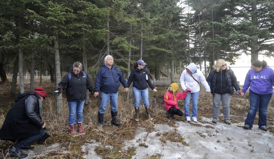 ADVANCE FOR WEEKEND APRIL 9-10, 2016 AND THEREAFTER -- In this March 24, 2016 photo, Kenaitze Indian Tribe members, students and Kenai Peninsula College faculty get ready for an opening prayer led by Dena'ina Elder Max Chickalusion Jr. at Kalifornsky Village, Alaska. The contrast of white cemetery crosses against the greens and browns of the surrounding forest in the distance is the first sign one has entered Kalifornsky Village. Many people who have lived in the area for years have probably driven by it without knowing the history and meaning the place holds in the community. (Megan Pacer/Peninsula Clarion via AP)  MANDATORY CREDIT