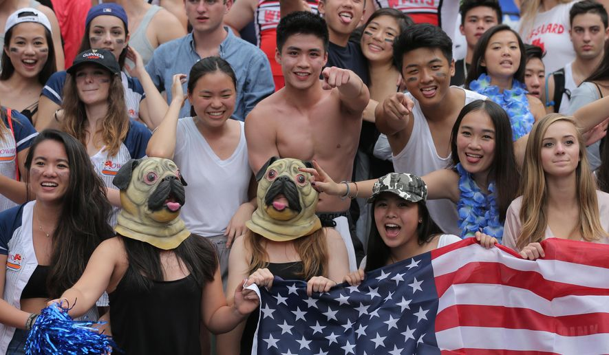 Rugby fans hold a U.S. national flag during a second day of the Hong Kong Sevens rugby tournament in Hong Kong, Saturday, April 9, 2016.  (AP Photo/Kin Cheung)