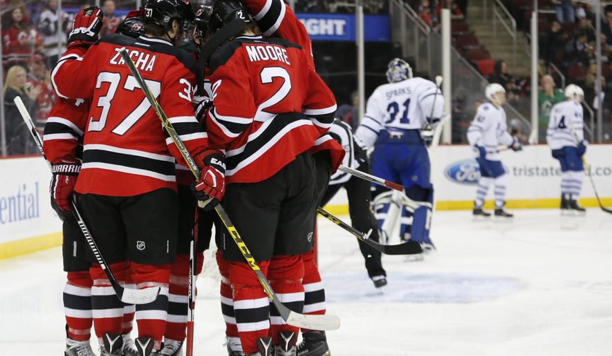 New Jersey Devils players celebrate a goal by center Adam Henrique (14) against the Toronto Maple Leafs during the second period of an NHL hockey game, Saturday, April 9, 2016, in Newark, N.J. (AP Photo/Julio Cortez)