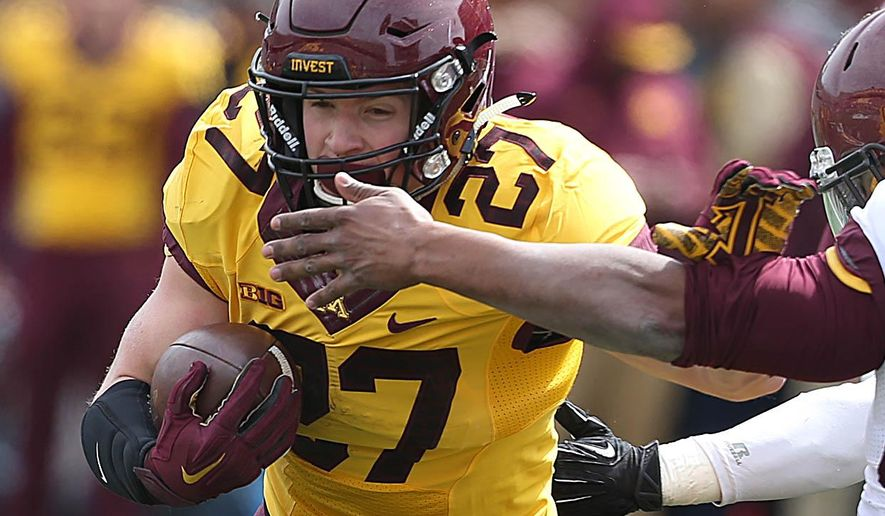 Minnesota's gold team running back James Johannesson breaks tackles for a gain in a spring NCAA college spring football game in Minneapolis on Saturday, April 9, 2016. (Jim Gehrz/Star Tribune via AP) MANDATORY CREDIT