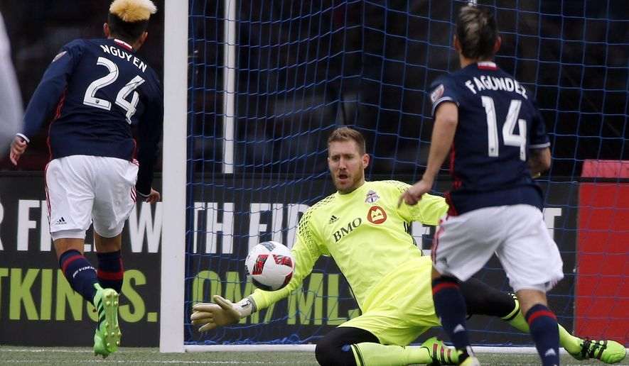 Toronto FC's Clint Irwin, center, blocks a shot in front of New England Revolution's Lee Nguyen (24) and Diego Fagundez (14) during the first half of an MLS soccer game in Foxborough, Mass., Saturday, April 9, 2016. (AP Photo/Michael Dwyer)